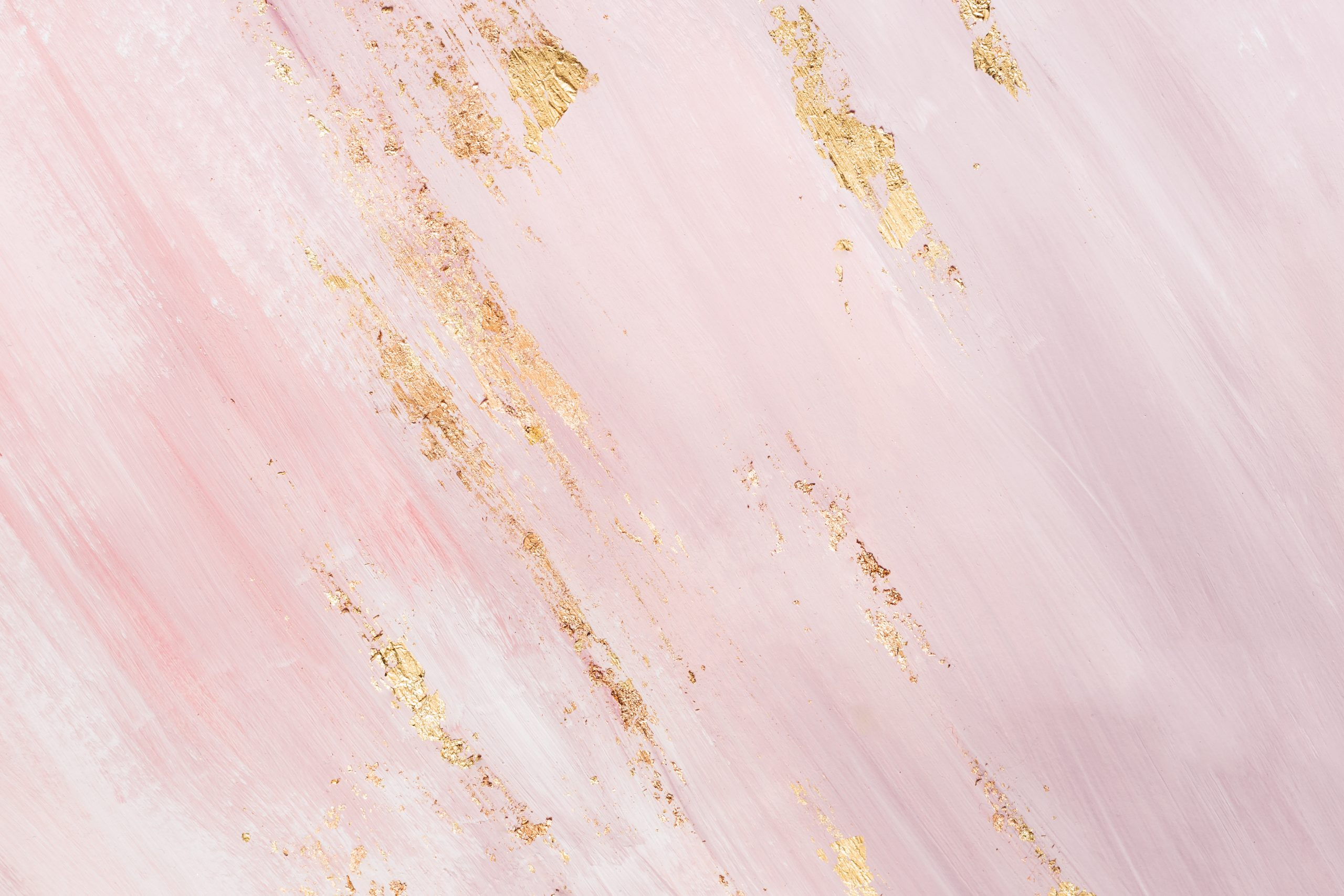 Delicate pink marble background with gold brushstrokes. Place for your design.